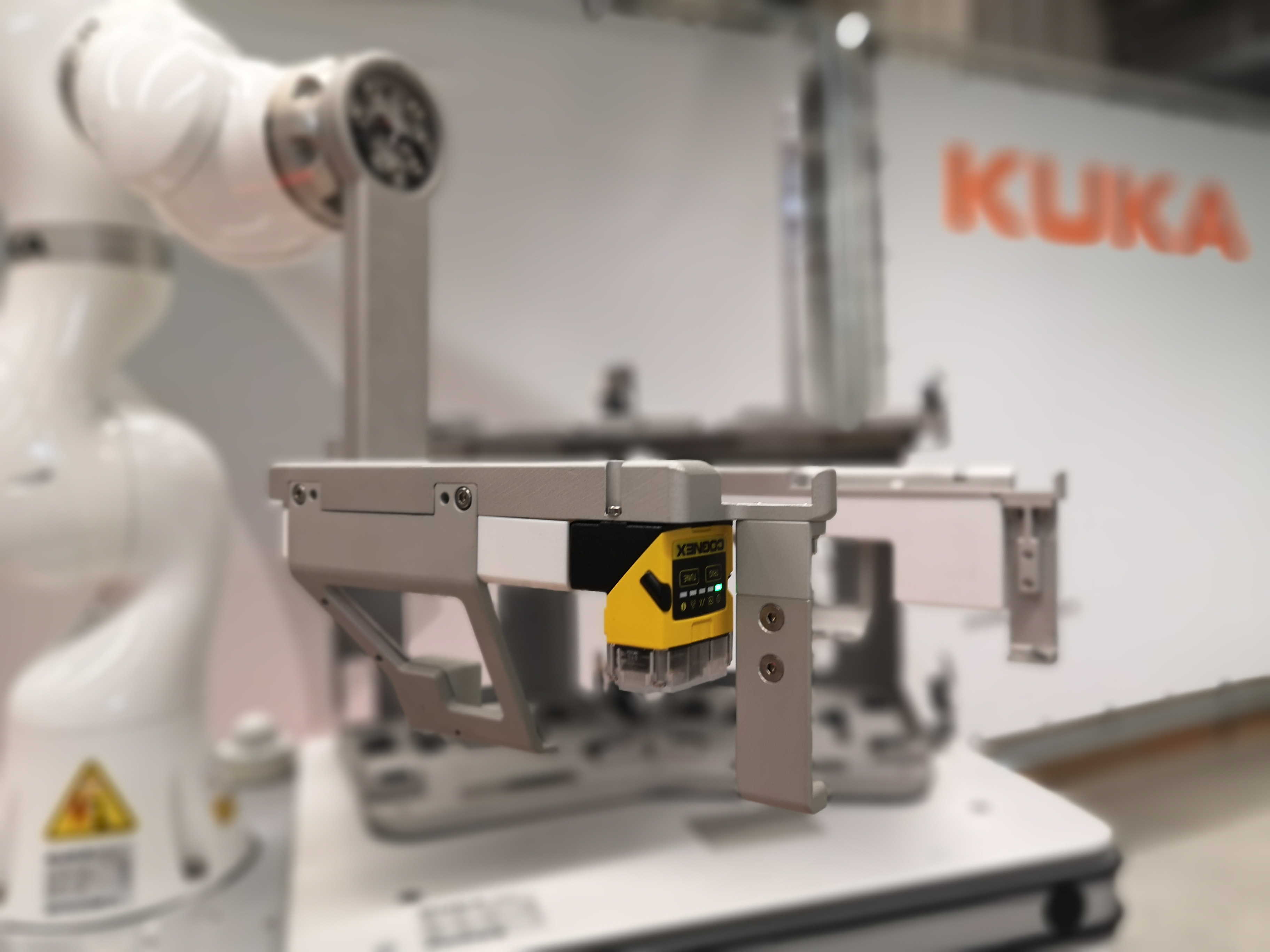 A KUKA robot with a machine vision camera mounted on its arm