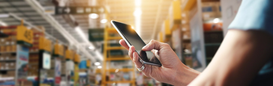 person using iPhone in manufacturing warehouse