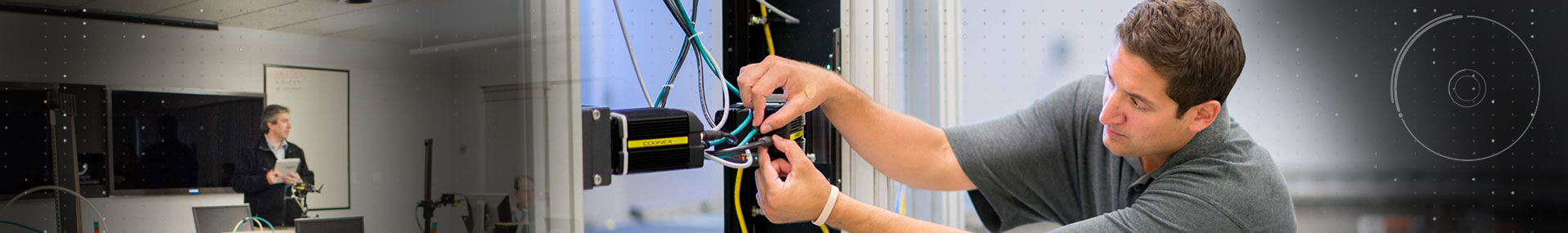 teacher in front of class and service technician adjusting cognex wires
