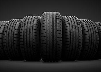 multiple standing tires against black background