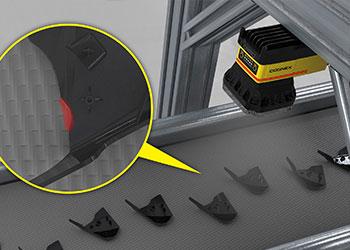 Système de vision en train d'identifier un défaut sur une pièce en plastique moulée par injection