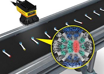 Cabeças de escova de dentes elétrica sendo inspecionadas em um transportador