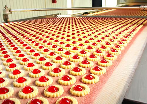 identical cookies with cherries on conveyor