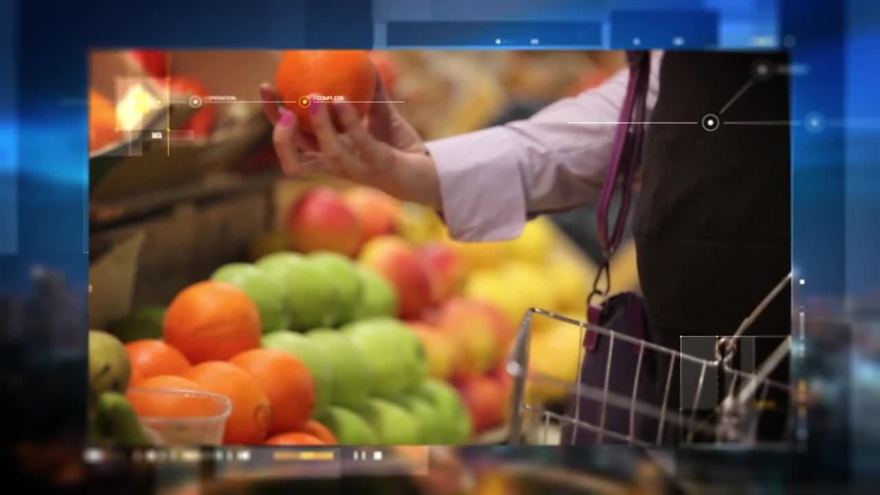 person shopping for fruit holds orange