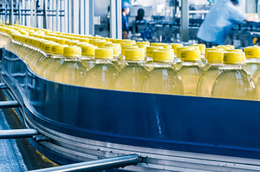 Yellow beverage bottles moving on blue conveyor in factory