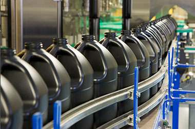 large black plastic jugs on manufacturing conveyor belt
