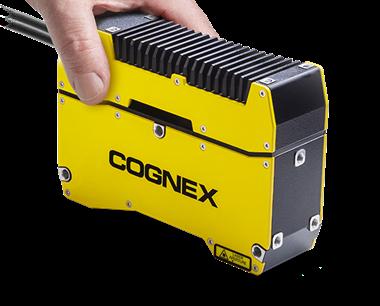 Das In-Sight 3D-L4000 Bildverarbeitungssystem wird von der linken Hand einer unbekannten Person sanft festgehalten.
