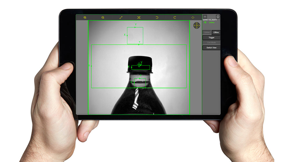 user holding tablet with beverage bottle inspection on Cognex WebHMI VisionView900 interface