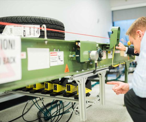 3D Tire Inspection using laser displacement sensors below conveyor belt with engineer testing setup