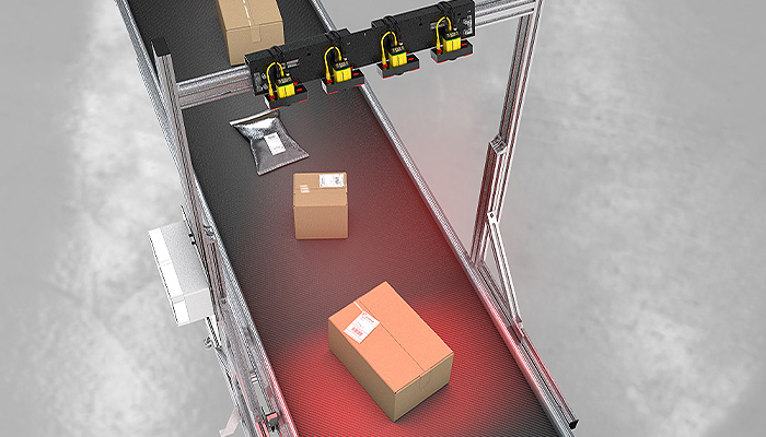 Boxes being scanned by a top-side barcode reading tunnel