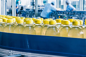 yellow beverage in plastic bottles on conveyor in factory with workers in background