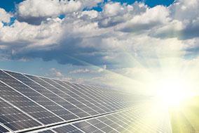 sun rising over row of solar panels