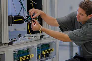 Man wiring up a Cognex 503 vision system