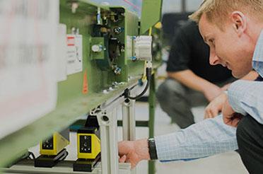 Cognex customer field representative inspecting laser profilers under conveyor