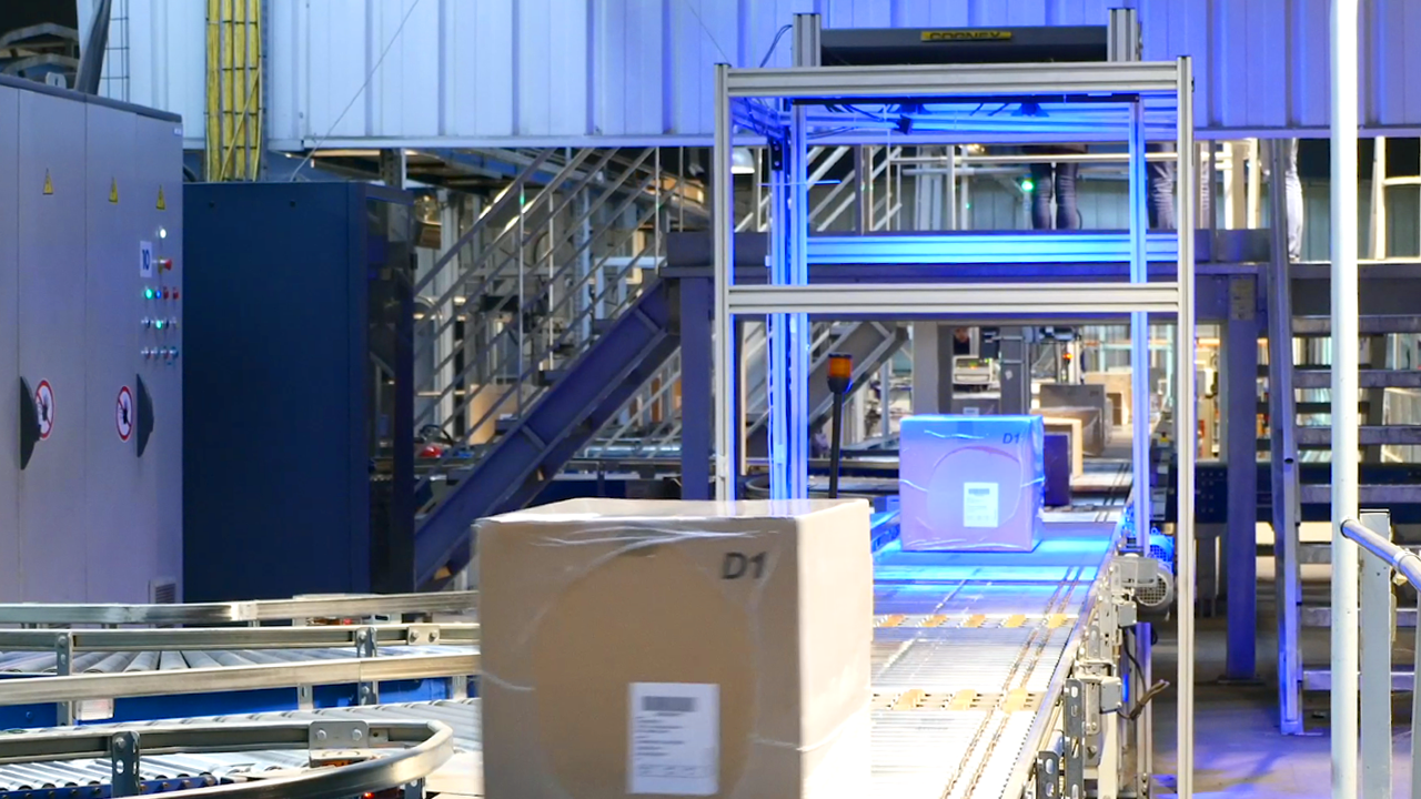 boxes moving down conveyor belt in warehouse setting