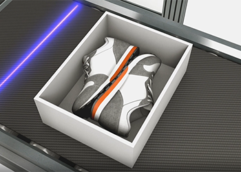 pair of shoes in box on conveyor belt approaching laser line